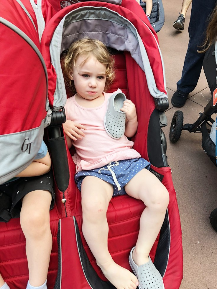 Grouchy toddler in stroller holding one shoe