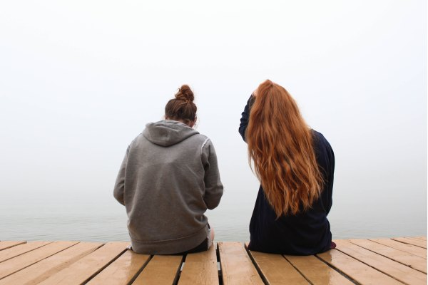 Two friends sitting on a dock